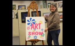"""Library Director Linda Roiger puts out the """"welcome sign""""  to the Juried Art Show. Everyone welcome."""