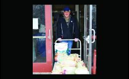 Springfield Area Food Shelf volunteer John Sagan is following new precautionary measures and takes groceries out to a clients vehicle.