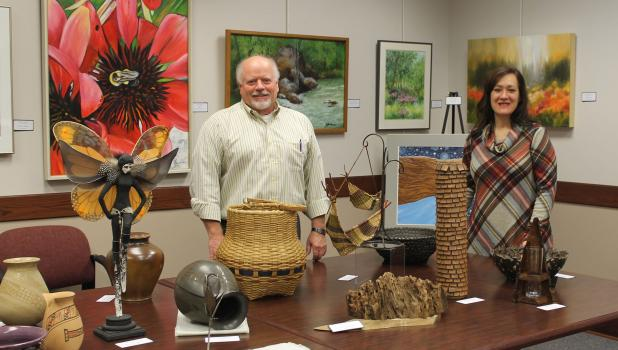 Tucker Loomis, a volunteer who helped hang the art in the Altermatt Gallery, Springfield Public Library, and librarian Rebecca Triplett are pictured with a few of the pieces being exhibited in the Juried Art Show.