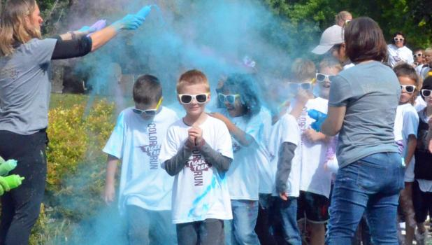 Springfield Elementary 2nd grader Tanner Petersen smiles with classmates Lincoln McCone and Sierra Medelez during last Friday's Tiger Trek Color Run.