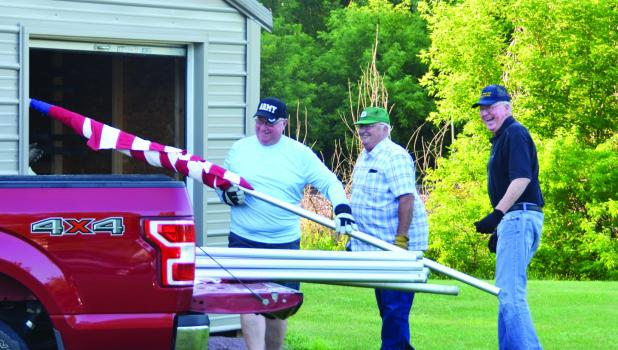 Springfield American Legion members Dan Skarp, Floyd Rogotzke and Tom Anderson share a laugh as they load up flags to be placed at the Avenue of Flags on the morning of July 4.