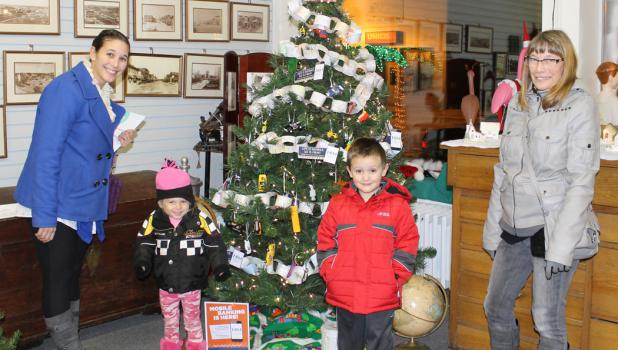 SAHS Festival of Trees displays clever themes! Little Aubrey Schilling and Logan Shoen found a Christmas tree that struck their fancy at the Springfield Museum.  The Farmers & Merchants Bank tree promotes mobile banking, and the tree is decorated with a variety of toy vehicles of all sorts. At left is Aubrey's mother, Christa Schilling, and at the right is Lisa Reiner.