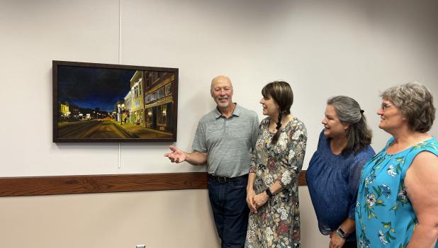 Springfield artist, Neil Neidt, shares the painting he's submitting to the Art Show to Sharon Pieschel, Springfield Public Library Board President; Wendy Krier, Springfield Public Library board member; and Linda Roiger, Head Librarian.
