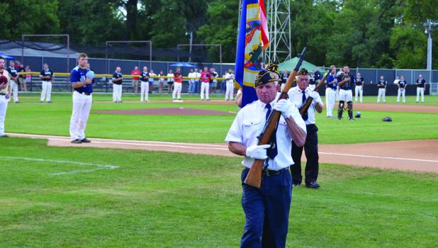 Springfield's American Legion Color Guard member Butch Krebs leads Jan Davidson, Chuck Roiger and Dale Potter off the baseball field during Friday night's game.