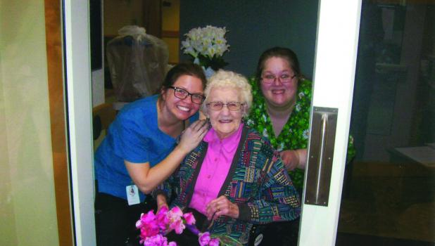 """Peggy Bredvold received birthday gifts with the help of nursing staff members Beki Gewerth and Jennifer Guetter in the lobby entrance of The Maples. On Saturday, Peggy was honored with a """"car parade"""" by her """"Coffee Ladies"""" group."""