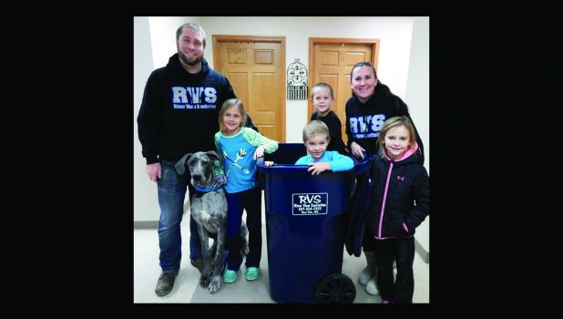 Brent and Rachel Kucera, their children, Caidence, Nathan (in the trash can), Nolan and Leah and their dog, Tito, are pictured with one of the trash cans that soon will be put into service in Springfield.