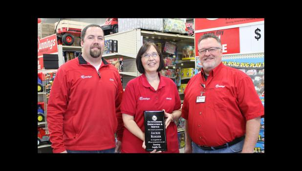 Jackie Roiger holds her recognition plaque from Runnings.  Former store manager Craig Valentin is pictured left, and the new store manager, John Aanenson, is at the right.