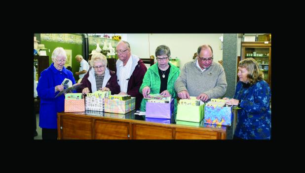 Looking over the collection of Little Golden Books for sale from Radel's collection — from left: Joan Carruthers, Ardis Nielsen, Roger Nielsen, Cheryl Diede, Tim Tauer and Kathy Pederson.