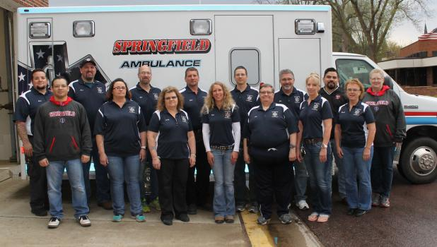 Springfield Ambulance Service – front, from left: Tony Linan, Lyn Johnson, Cindy Gewerth, Kimberly Jahnke, Al Larson, Laurie Cook, and Brenda Anderson. Back: Team Captain Adam Grant, Dave Wahl, Rick Cook, John Roiger, Cliff Heglund, John Nicholson, Lupe Trevino, and Cathy Lang. Crew members not pictured include Paula Barnes, Elsie Groebner, Kris Lorenzen, and Nick Weisensel.