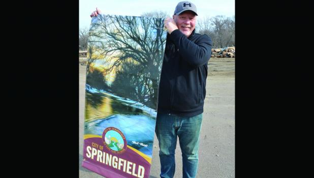 Local artist Neil Neidt is pictured holding a banner with one of his popular pieces of art work on it.