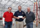 Brian Vogt, Cargill Ag Marketing Services personal marketing manager of Wayzata,  left, and Scott Johnson, Springfield, Cargill AgHorizons farm marketer, right, present FFA Advisor T.J. Brown with a check for $7,500 to help equip the school's new greenhouse.