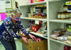 Deb Rasset organizes items at the food shelf's new location.